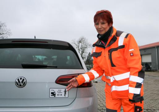 Bauhof-Vorarbeiterin Sabine Saboth präsentiert den neuen Aufkleber für mehr Verkehrssicherheit.